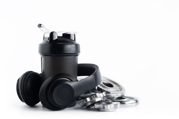 白で隔離されるヘッドフォンとクロムプレートダンベルとホエイプロテインシェーカーボトル