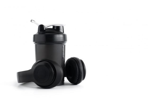白い背景で隔離のヘッドフォンとホエイプロテインシェーカーボトル