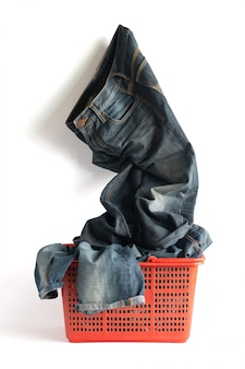 服やクリッピングパスと白い背景で隔離の色あせたジーンズパンツでいっぱいのバスケットを洗う