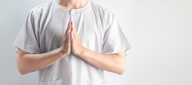 Молящиеся рукиазиатские мужчины в белой повседневной одежде изолированы, религия и медитация