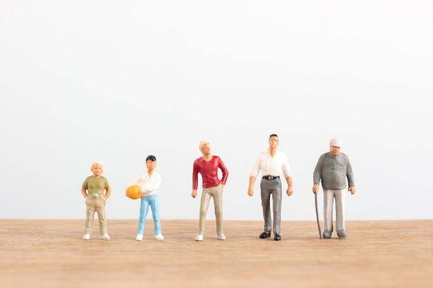 さまざまな年齢のミニチュアの人々は、白い背景を持つ木製の床の上に立つ