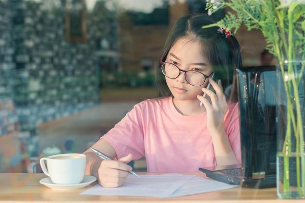 ラップトップコンピュータとコーヒーショップデスクに座って携帯電話で話すメガネのアジアの女の子