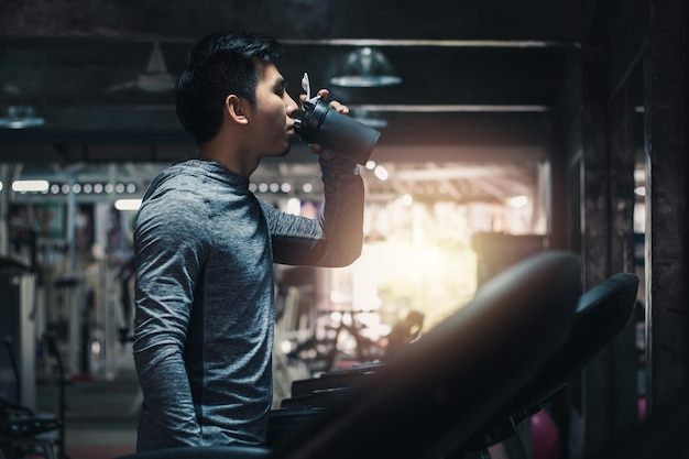 Молодой красивый человек, осуществляющих кардиотренировки на беговой дорожке с питьевой сывороткой в тренажерном зале