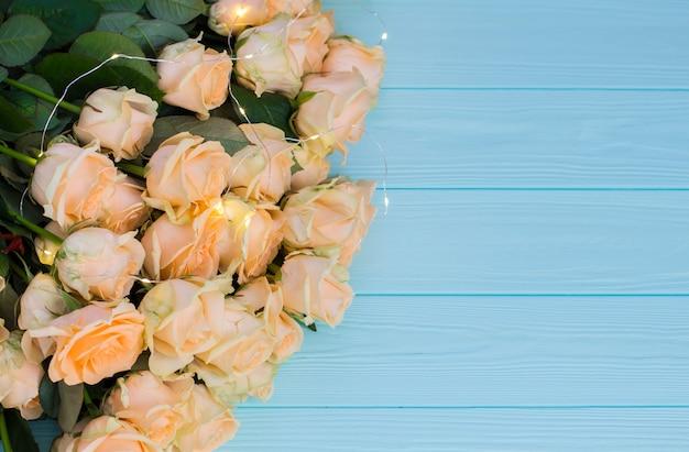 木製の青緑色の背景にピーチのバラ