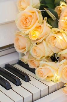 白いピアノに花輪の桃のバラ