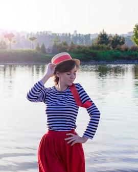 水の近くの麦わら帽子の少女