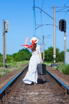 鉄道線路上の古いスーツケースを持つ少女。かわいい女の子がスーツケースを持って歩いています。後ろからの眺め。赤いリボンと長いドレスのカナッペ帽子のティーンエイジャー。