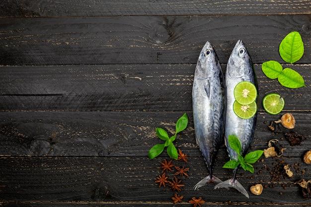 暗い黒の木製の背景、スパイスと野菜の魚の新鮮なカツオ魚
