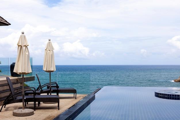 熱帯の海を見渡せるスイミングプールと屋外のビーチチェア