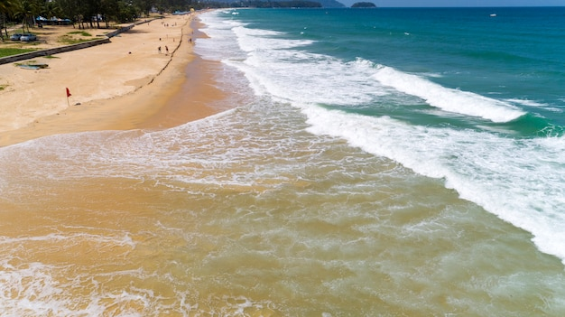 美しい熱帯の海とプーケットタイのカロンビーチで砂浜に打ち寄せる波空撮ドローンショット