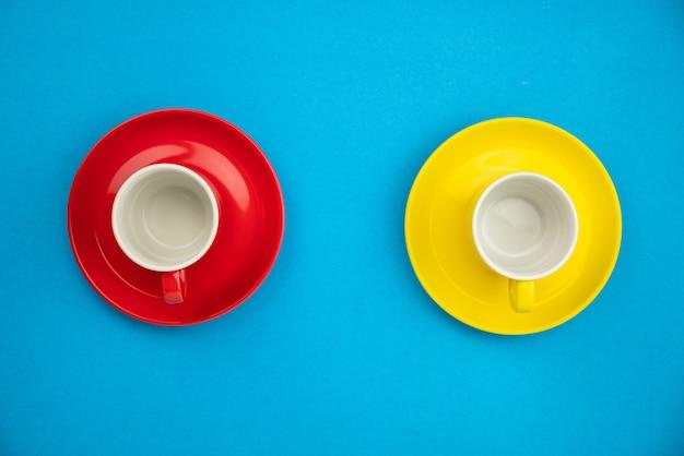 青い紙の背景にカラフルなコーヒーカップ