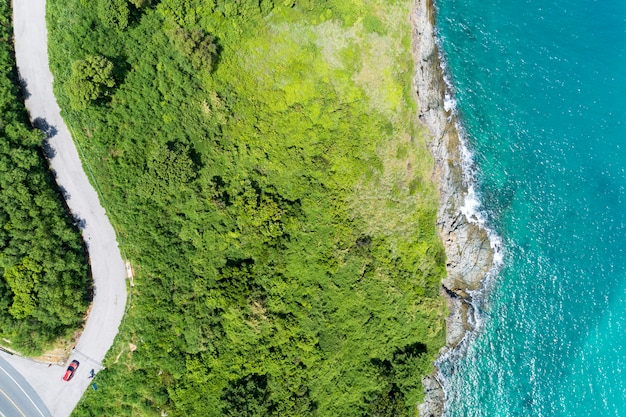 Асфальт сельской дороги кривой на высокой горе с тропическим морем