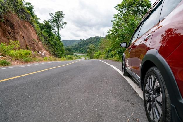 Красный внедорожник на асфальтированной дороге с горным зеленым лесом транспорт