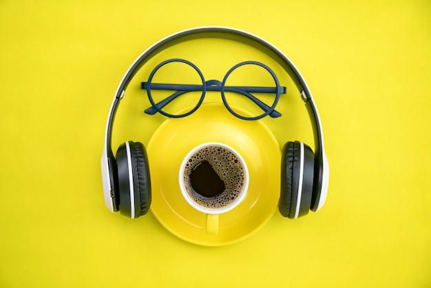 黄色の紙の背景にヘッドフォンと教師のメガネとコーヒーカップ