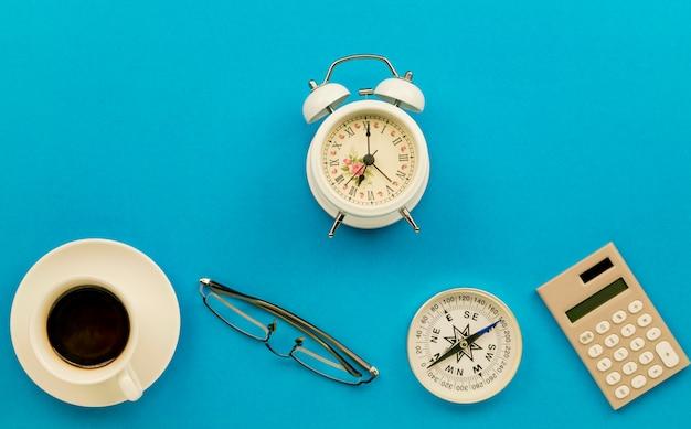 白いコーヒーカップ、メガネ、コンパス、電卓、ビンテージの白い目覚まし時計のビジネスオブジェクトとビジネスオフィスのテーブル