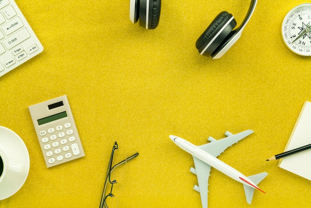 電卓、白い目覚まし時計、コンパス、飛行機モデル、ゴールドラメのテクスチャに輝くコーヒーカップとヘッドフォン