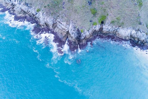 岩の海岸に打ち寄せる波と海景の空撮ドローン写真ビュー