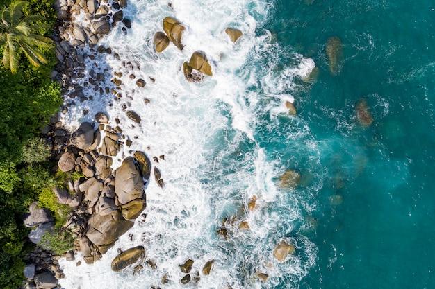 空撮ドローン高角度のビューで岩の自然の風景と夏の季節の海の海岸の景色と美しい熱帯の海に砕ける波の空撮