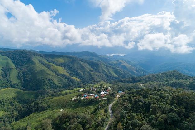 Аэрофотоснимок кривой дороги на тропических лесах горы, изображение птичьего полета над облаками удивительный ландшафт природы с облаками и горными вершинами