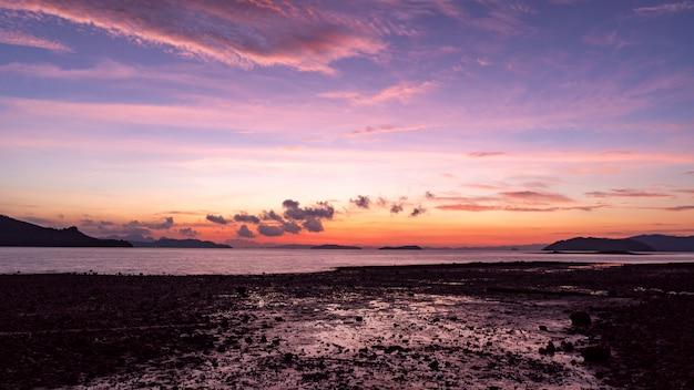 夕日や日の出の風景の岩と劇的な空海景の長時間露光画像