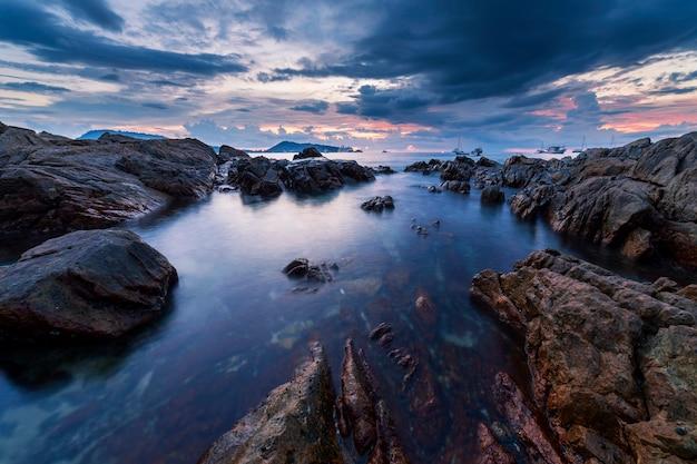 日没の風景の中の岩と劇的な空海景の長時間露光画像