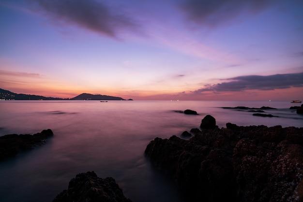 Изображение долгой выдержки драматического неба с утесом в пейзаже захода солнца