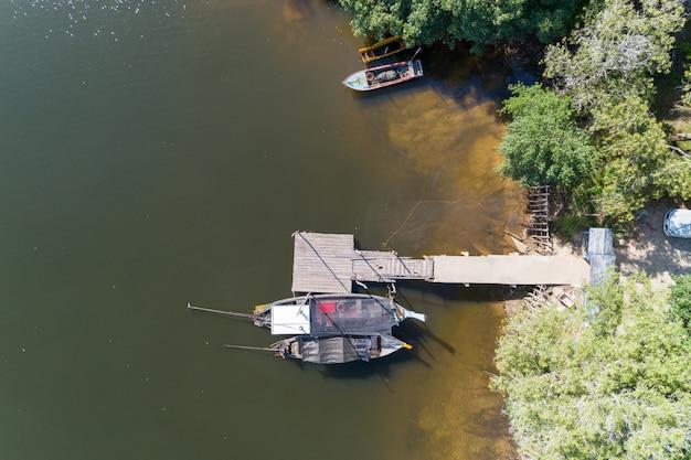 空撮トップダウン運河のロングテール漁船の高角度ビュードローンショット。