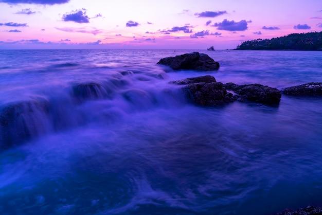 劇的な空の海の日の出や日没の風景の長時間露光画像ビュー美しい光の自然と岩の上の砕ける波。