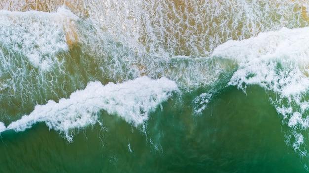 Вид сверху природный ландшафт из плавной волны белого цвета морского пена бирюзовые волны красивое тропическое море в летнем сезоне изображение с высоты птичьего полета дрон выстрел, высокий угол обзора сверху вниз.