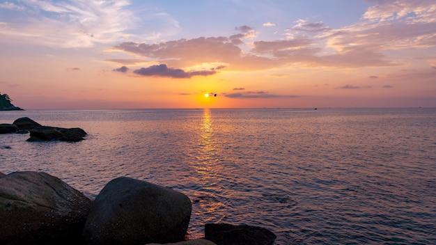 前景の日没の風景の岩と劇的な空の海の景色。