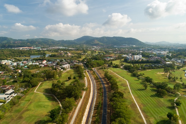 空撮ドローンショットによる緑のゴルフ場の写真の周りのアスファルト道路。