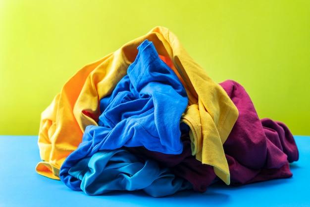 Куча грязной прачечной одежды на синем столе желтый фон.