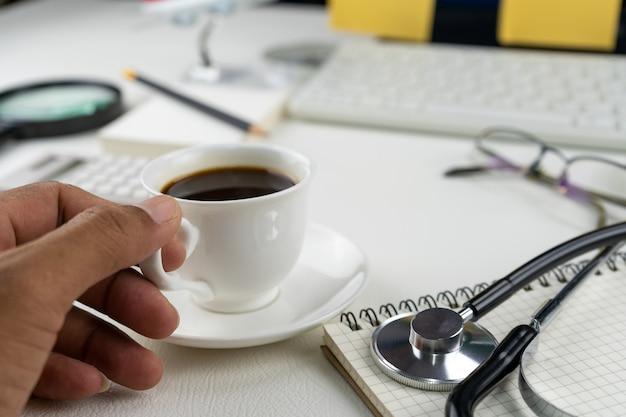 Вручите держать кофейную чашку с объектами дела на таблице белой кожи.