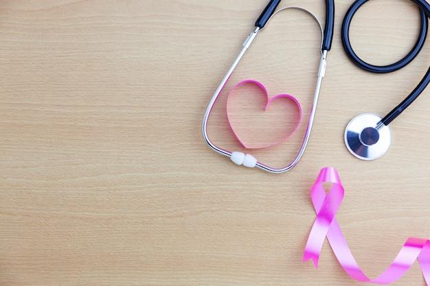 世界保健デーの背景、木製のテーブル背景にハートリボンと聴診器のヘルスケアと医療の背景概念。