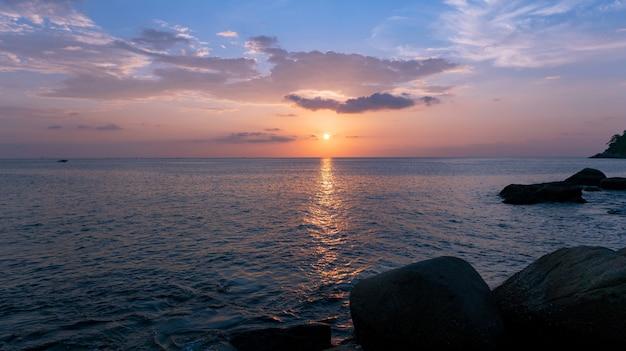 自然の驚くべき美しい光夕日や日の出の風景の背景の前景の岩と劇的な空の海。