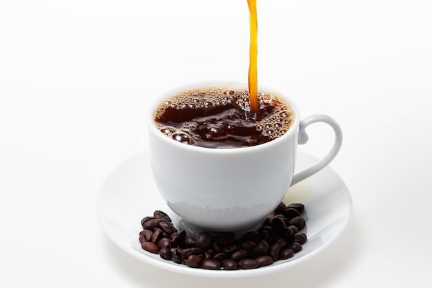 白いコーヒーカップと白い背景に豆にコーヒーを注ぐ