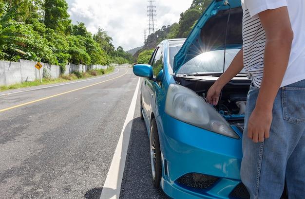 Человек, стоящий на дороге с неисправным двигателем автомобиля в середине дороги
