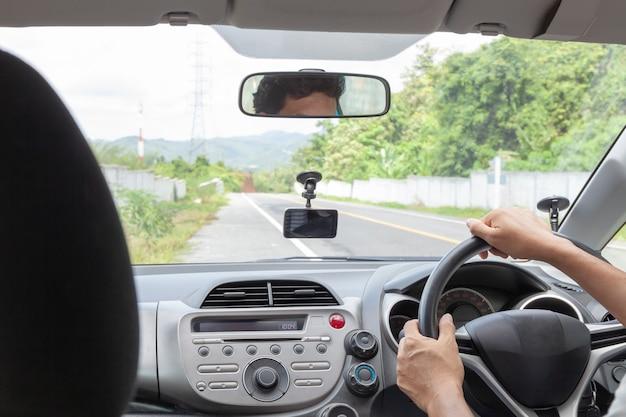 アスファルト道路で車を運転するステアリングホイールを握って手の男性