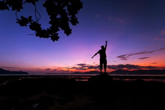 熱帯の海の石の上に立って、日の出の間に風景を楽しんでいる一人の男観光客