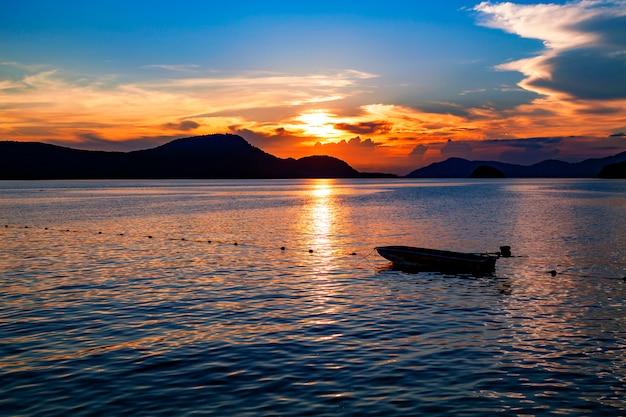 海の夕日の風景の中の小さな漁船