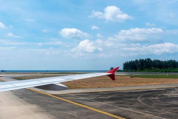 飛行機の翼を飛行し、航空機の窓から滑走路の空港で離陸