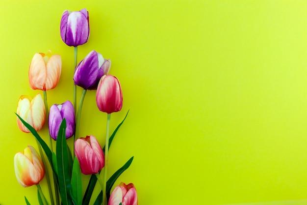 黄色の背景にマルチカラーチューリップの春の花、フラットは母の日、バレンタインデー、女性の日のホリデーグリーティングカードの画像を置く