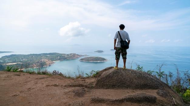 Путешественник стоит и думает что-то и видит красивый пейзаж пейзаж