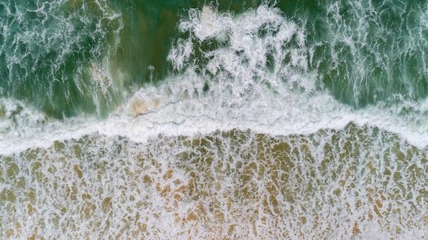 ビーチ空撮ドローンショットに打ち寄せる波と熱帯の海