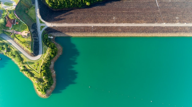 ダム、美しい自然の風景の周りのアスファルト道路の飛行ドローンからの空中写真