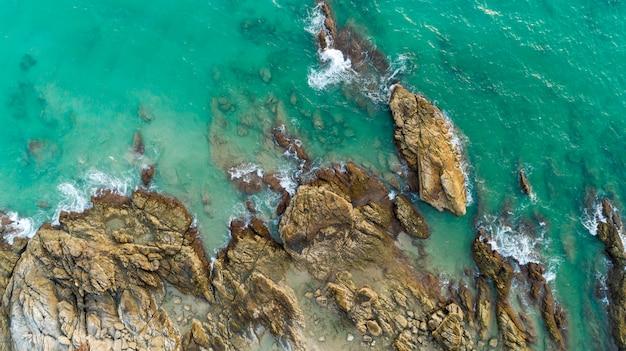岩に打ち寄せる波とタイのプーケットのビーチから風光明媚な海の景色の空撮ドローンショット