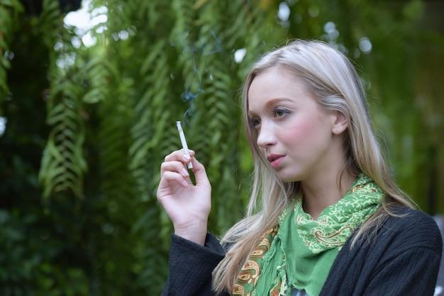 Портрет красивой молодой женщины, курить сигареты. опасности для здоровья.