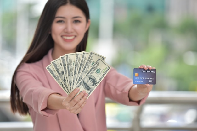 ピンクの服を着たアジアの女の子クレジットカードを持った手に甘い笑みを浮かべてください。