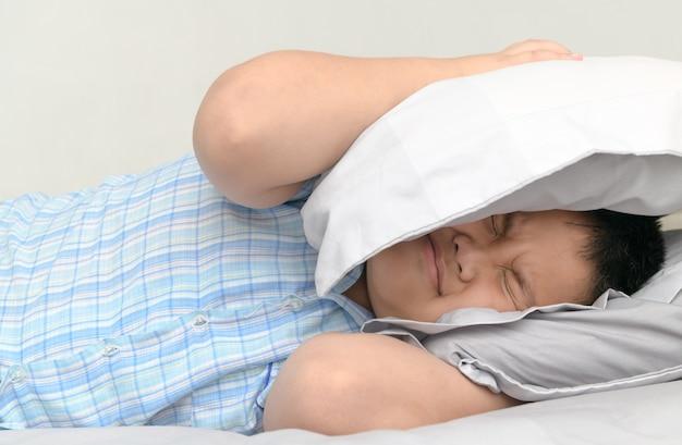 あまりにも大きな迷惑な騒音が彼の上を保持するため、枕で頭をカバーしてベッドに横たわって肥満脂肪男の子