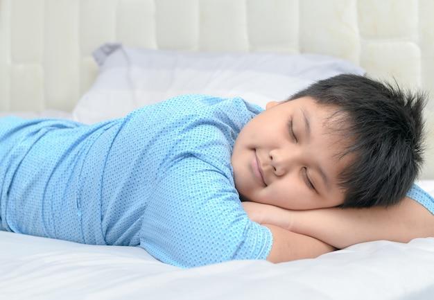 Оживленный толстяк сладкий сон на руке на кровати, здоровая концепция